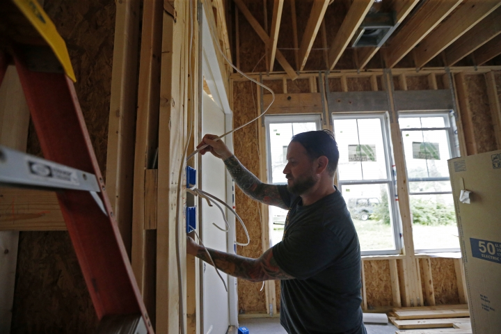 In this Friday, March 24, 2017, photo, Quinn Lovetro, an electrician with Tasch Electric, works on a home being built by Zach Tyson of Tyson Construction, in Destrahan, La. General contractors and other small businesses in the remodeling industry can look forward to strong growth in the coming years, but the big force behind that business may be surprising: baby boomers. Tyson estimates that between 30 percent and 40 percent of his revenue is coming from boomer renovations, up from 15 percent to 20 percent five years ago. (AP Photo/Gerald Herbert)