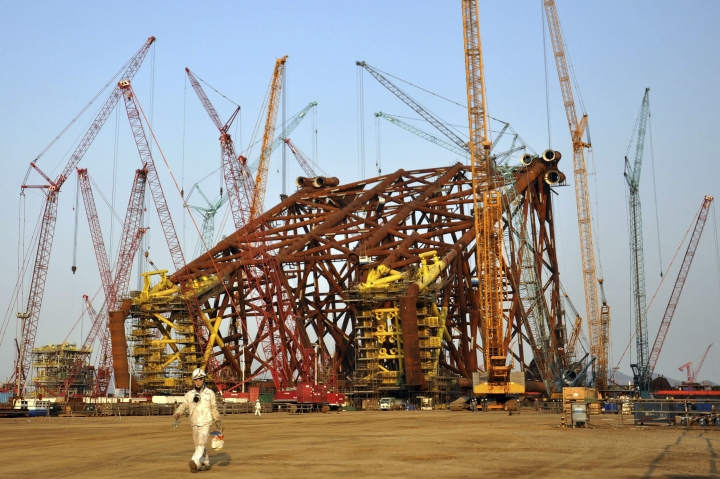 In this March 31, 2017 photo, a worker walks past construction at a subsidiary of China Offshore Oil Engineering Co. Ltd. in Qingdao in eastern China's Shandong province. Asia's developing economies will see steady growth this year and the next, though the evolving policies of President Donald Trump's administration are a major uncertainty, according to the Asian Development Bank's latest report released Thursday, April 6, 2017. (Chinatopix via AP)
