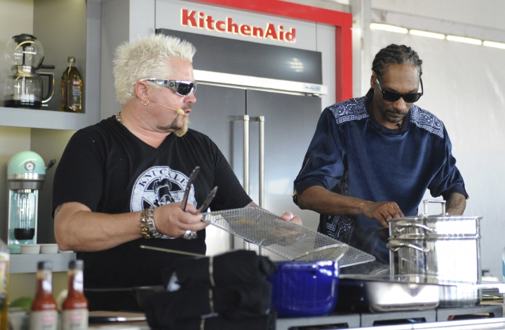 "This Feb. 26, 2017 photo made available by WorldRedEye.com, shows rapper Snoop Dog, right, and Chef Guy Fieri, cooking together during a demonstration at the South Beach Wine & Food Festival in Miami Beach, Fla. Rappers Snoop, Action Bronson and Rev Run are ushering the culinary world into an era where shows like """"Martha and Snoop's Potluck Dinner Party"" are a hit and rappers like 2 Chainz drop cookbooks along with their albums. (Ryan Troy/WorldRedEye.com via AP)"