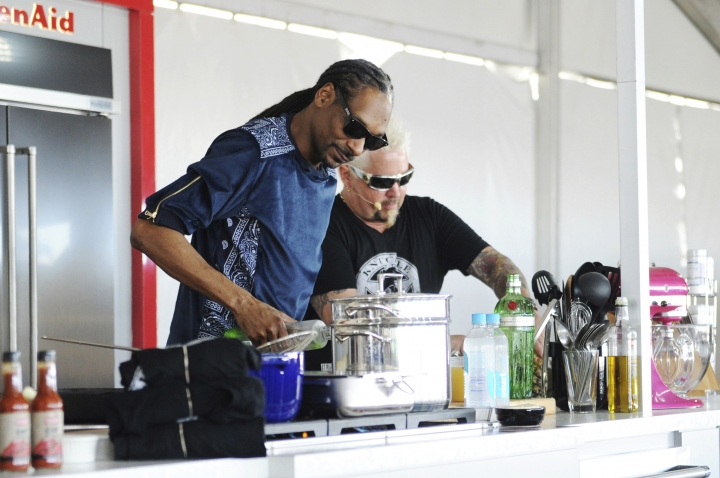 "This Feb. 26, 2017 photo made available by WorldRedEye.com shows rapper Snoop Dog, left, and Chef Guy Fieri cooking together during a demonstration at the South Beach Wine & Food Festival in Miami Beach, Fla. Rappers Snoop, Action Bronson and Rev Run are ushering the culinary world into an era where shows like """"Martha and Snoop's Potluck Dinner Party"" are a hit and rappers like 2 Chainz drop cookbooks along with their albums. (Ryan Troy/WorldRedEye.com via AP)"