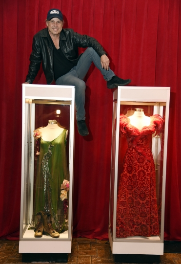 "Todd Fisher, son of the late actress Debbie Reynolds, poses atop glass cases displaying two dresses that Reynolds wore in the 1964 film ""The Unsinkable Molly Brown,"" at the Hollywood Roosevelt Hotel on Wednesday, April 5, 2017, in Los Angeles. Fisher considers himself the custodian of Debbie Reynolds' and Carrie Fisher's legacies. He says it's a role he's always played, but now it's helping him process the grief of losing his mother and sister. (Photo by Chris Pizzello/Invision/AP)"