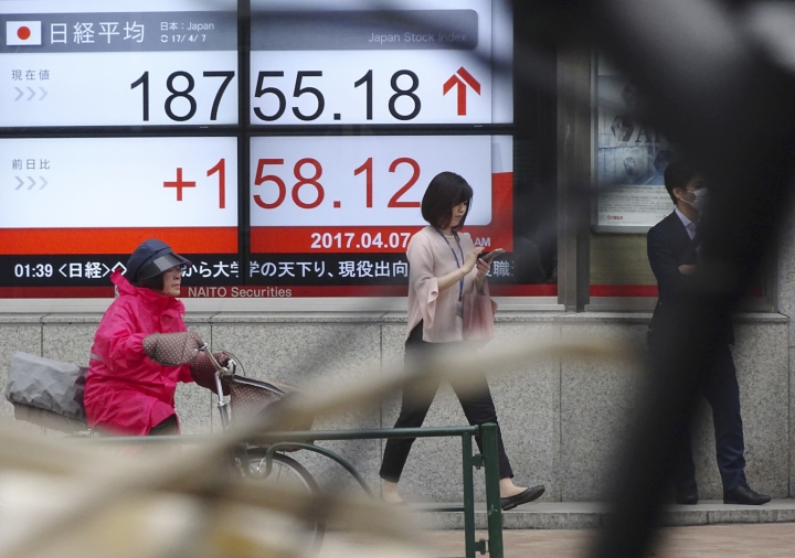 People riding a bicycle, walking and standing by an electronic stock board showing Japan's Nikkei 225 index at a securities firm are seen through a passing bicycle wheel in Tokyo, Friday, April 7, 2017. Asian stock indexes sank Friday as the U.S. fired missiles at a Syrian air base during President Donald Trump's first meeting with China's president, leaving investors on edge over the global outlook. (AP Photo/Eugene Hoshiko)