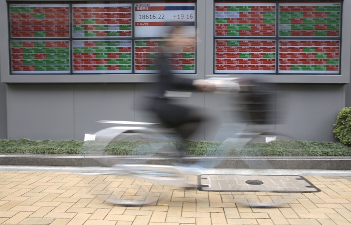 A woman rides a bicycle in front of an electronic stock board showing morning closing transaction value of Japan's Nikkei 225 index at a securities firm in Tokyo, Friday, April 7, 2017. Asian stock indexes sank Friday as the U.S. fired missiles at a Syrian air base during President Donald Trump's first meeting with China's president, leaving investors on edge over the global outlook. (AP Photo/Eugene Hoshiko)