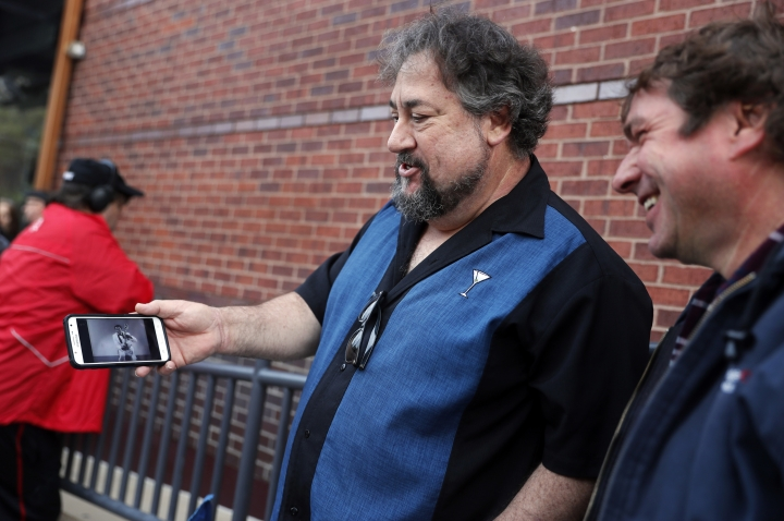 "Alan Bozich, left, holds up his phone to watch a video of Chuck Berry as he stands in line with Jimmy Herrmann, right, to pay their respects to the rock 'n' roll legend during Berry's public viewing Sunday, April 9, 2017, in St. Louis. The man behind such classics as ""Johnny B. Goode,"" ''Sweet Little Sixteen"" and ""Roll Over Beethoven"" died on March 18 at the age of 90. (AP Photo/Jeff Roberson)"