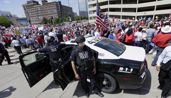 Dallas police stand guard during a protest march through downtown Dallas, Sunday, April 9, 2017. Thousands of people are marching and rallying in downtown Dallas to call for an overhaul of the nation's immigration system and end to what organizers say is an aggressive deportation policy. (AP Photo/LM Otero)