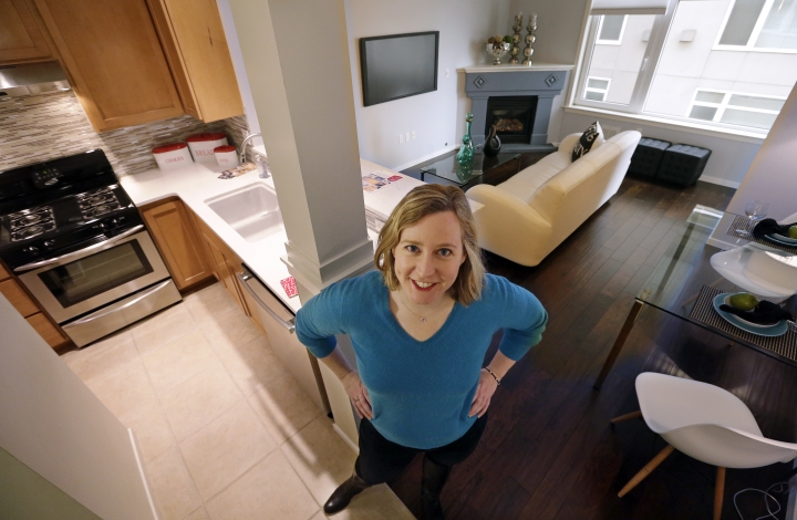 In this Thursday, March 30, 2017, photo, Kathleen Mulcahy stands in her recently sold one-bedroom condo, on which she received nearly two dozen offers and sold for more than $100,00 over her asking price, in Seattle's Belltown neighborhood. Many would-be buyers, especially in the big cities, will be wading into a market that's crowded with rival buyers and constrained by the lowest inventory of homes for sale in nearly two decades. That severe imbalance between supply and demand favors sellers, but also gives homeowners little incentive to part with their properties. (AP Photo/Elaine Thompson)