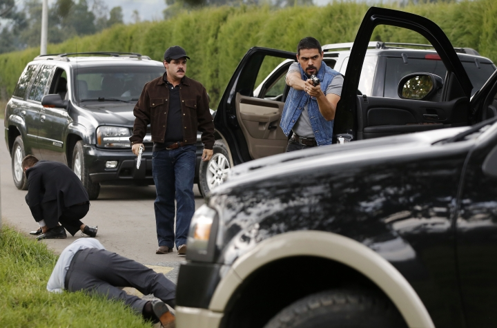 """In this March, 21, 2017 photo, Mexican actor Marco de la O, back left, plays drug lord Joaquin Guzman during the filming of """"El Chapo"""" in Tabio, Colombia. At the time filming started, Guzman was still in Mexico and the series' location was shifted for security reasons, said producer Daniel Posada. """"Colombia was a good option, because we have well-trained crews and it is very similar in appearance to Mexico."""" (AP Photo/Fernando Vergara)"""
