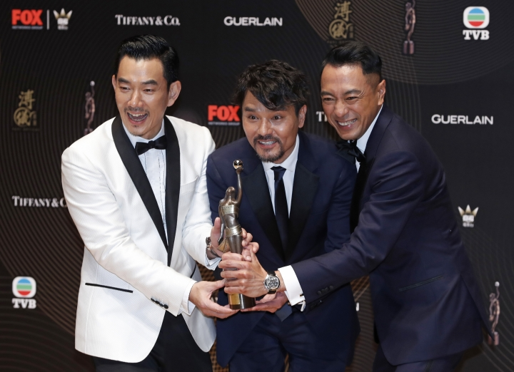 Hong Kong actor Gordon Lam, center, poses with his colleagues actors Philip Keung, right, and Richie Ren after winning the Best Actor award during the Hong Kong Film Awards in Hong Kong, Sunday, April 9, 2017. (AP Photo/Kin Cheung)