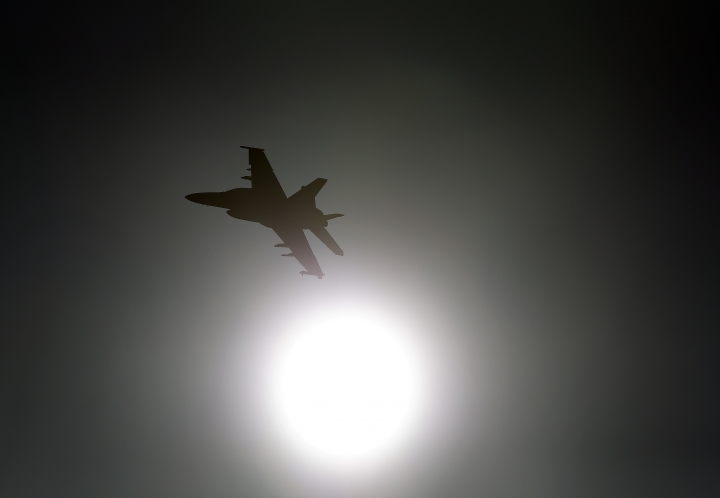 """In this Feb. 28, 2017, photo, Thomas """"Tom"""" P. McGee of the VX-9 Vampire squadron from Naval Air Weapons Station China Lake, flies an F/A-18E Super Hornet toward the sun over Death Valley National Park, Calif. Military jets roaring over national parks have long drawn complaints from hikers and campers. But in California's Death Valley, the low-flying combat aircraft skillfully zipping between the craggy landscape has become a popular attraction in the 3.3 million acre park in the Mojave Desert, 260 miles east of Los Angeles. (AP Photo/Ben Margot)"""