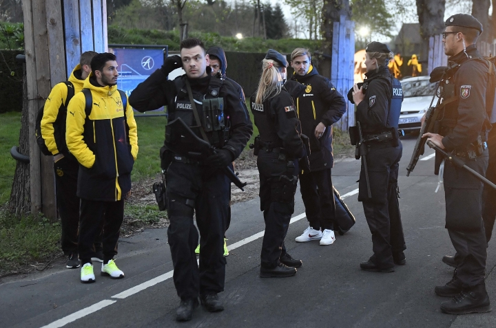 Dortmund's Marcel Schmelzer talks to police officers outside the team bus after it was damaged in an explosion before the Champions League quarterfinal soccer match between Borussia Dortmund and AS Monaco in Dortmund, western Germany, Tuesday, April 11, 2017. (AP Photo/Martin Meissner)