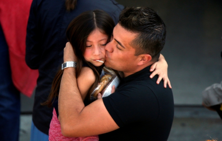A student who was evacuated after a shooting at North Park Elementary School is embraced after groups of them were reunited with parents waiting at a high school in San Bernardino, California. REUTERS/Mario Anzuoni