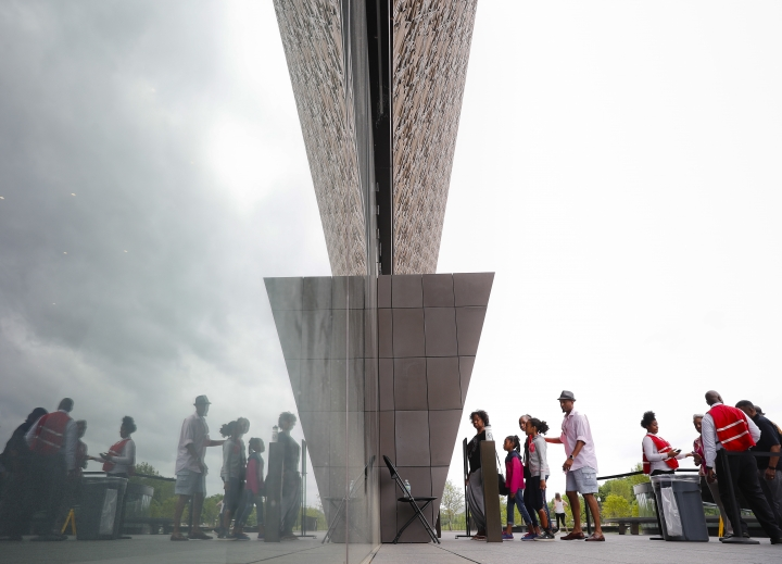 FILE - In this May 1, 2017 file photo, visitors are reflected as they enter the Smithsonian National Museum of African American History and Cultural on the National Mall in Washington. The number of U.S. tourists visiting Washington reached 20 million for the first time in 2016, thanks in part by a high-profile new museum on the National Mall, the city's tourism bureau announced. (AP Photo/Pablo Martinez Monsivais, File)