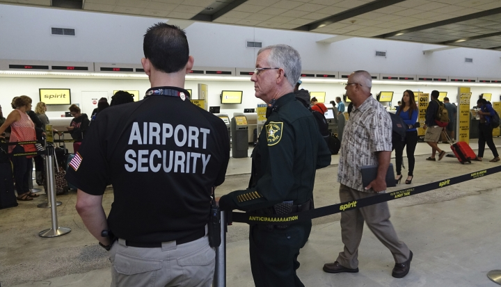 Airport Security and a Broward Sherriff's Deputy keep an eye on the line at Spirit Airlines, Tuesday, May 9, 2017, at the Fort Lauderdale-Hollywood International Airport in Fort Lauderdale, Fla. Skirmishes involving irate passengers broke out at the Florida airport Monday following the cancellation of multiple Spirit Airlines flights. (Joe Cavaretta/South Florida Sun-Sentinel via AP)