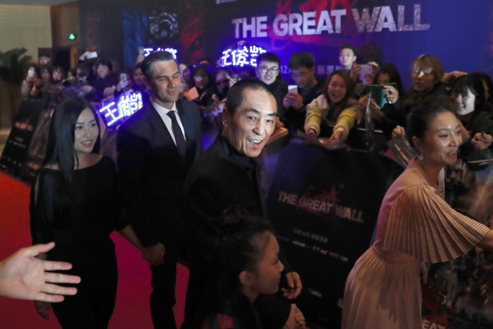"FILE - In this Dec. 6, 2016 file photo, movie director Zhang Yimou, center, arrives at a red carpet event for the movie ""The Great Wall"" at a hotel in Beijing. During an interview on Tuesday, May 9, 2017, Zhang says the disappointing U.S. performance of the biggest budget China-U.S. co-production to date, ""The Great Wall,"" may have been down to a weak story. Nevertheless, Zhang called the fantasy epic a ""first step"" in such collaborations and hoped filmmakers wouldn't be put off. (AP Photo/Andy Wong, File)"