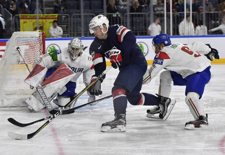 US forward J.T. Compher challenges for the puck during the Ice Hockey World Championships group A match between USA and Italy at the LANXESS arena in Cologne, Germany, Wednesday, May 10, 2017. USA won the match with 3-0. (AP Photo/Martin Meissner)