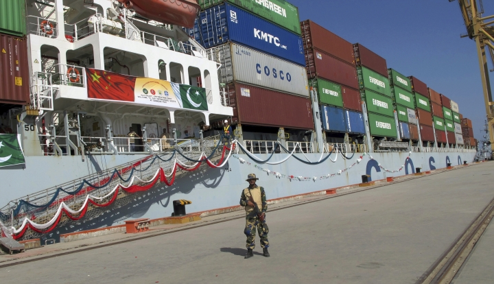 FILE - In this Nov. 13, 2016 file photo, a Pakistan Navy soldier stands guard while a loaded Chinese ship prepares to depart from Gwadar port that links to China's far western region on a new international route exporting goods to the Middle East and Africa, about 700 kilometers (435 miles) west of Karachi. Pakistan. China's new Silk Road initiative is ramping up as President Donald Trump focuses on domestic issues, downplaying foreign affairs. (AP Photo/Muhammad Yousuf, File)