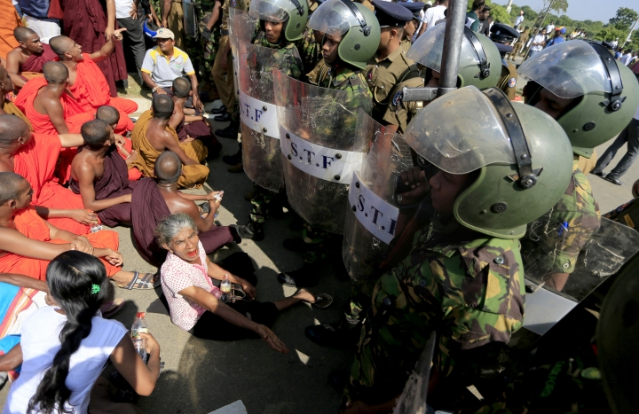 """FILE - In this Jan. 7, 2017 file photo, Sri Lankan Buddhist monks and villagers face government soldiers and shout slogans to protest a plan to take over private land for an industrial zone in which China will have a major stake outside the inauguration ceremony for the industrial zone in Mirijjawila village in Ambalantota, Sri Lanka. Critics of the Chinese initiative to build a """"new Silk Road"""" of ports, railways and roads to expand trade in a vast arc of countries across Asia, Africa and Europe, worry that China might undermine human rights, environmental and other standards for lending or leave poor countries burdened with debt. (AP Photo/Eranga Jayawardena, File)"""