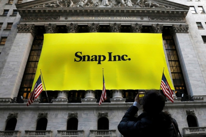 A woman photographs a banner for Snap Inc. on the facade of the New York Stock Exchange (NYSE) on the morning of the company's IPO in New York City, NY, U.S. March 2, 2017. REUTERS/Brendan McDermid