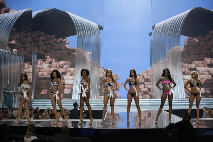 In this May 11, 2017, photo, Miss Connecticut USA Olga Litvinenko, center, competes with others during a preliminary competition for Miss USA in Las Vegas. Olga Litvinengo, who emigrated from Ukraine, speaks three languages and owns her own small business. Five of the contestants vying for the Miss USA title this year were born in other countries and now U.S. citizens. (AP Photo/John Locher)
