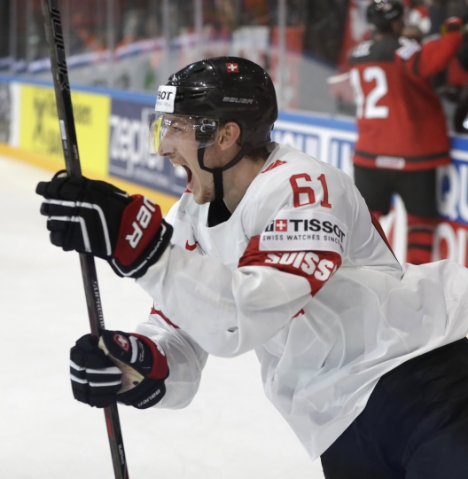 Switzerland's Fabrice Herzog celebrates after scoring his sides winning goal during the Ice Hockey World Championships group B match between Canada and Switzerland in the AccorHotels Arena in Paris, France, Saturday, May 13, 2017. (AP Photo/Petr David Josek)