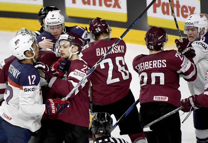 Latvia and US players scuffle during the group A hockey match between Latvia and USA at the 2017 Hockey World Championships in Cologne, Germany, Saturday, May 13, 2017. (Monika Skolimowska/dpa via AP)