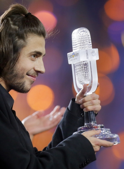 """Salvador Sobral from Portugal celebrates as he holds the trophy after winning the Final of the Eurovision Song Contest with his song """"Amar pelos dois"""", in Kiev, Ukraine, Saturday, May 13, 2017. (AP Photo/Efrem Lukatsky)"""