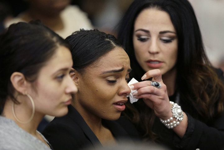 FILE - In this, April 14, 2017, file photo, Shayanna Jenkins Hernandez, center, the fiancee of former New England Patriots tight end Aaron Hernandez, is comforted as she reacts to Hernandez's double murder acquittal at Suffolk Superior Court Friday in Boston. Hernandez was found hanged in his prison cell on April 19, days while serving a life sentence for the 2013 killing of Odin Lloyd. (AP Photo/Stephan Savoia, Pool, File)
