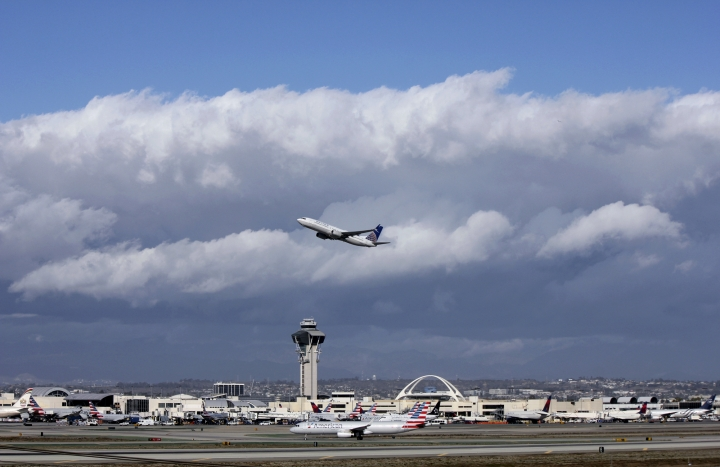 FILE- In this Nov. 27, 2016, file photo, a plane flies over Los Angeles International Airport. A $22 million facility at the airport called the Private Suite opened Monday, May 15, 2017, and offers an exclusive entrance, one-on-one security screening and plush lounges. (AP Photo/John Antczak, File)