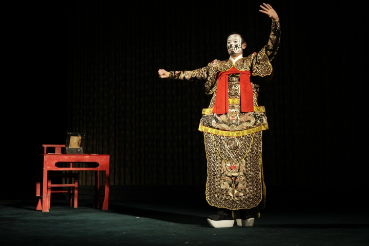In this Saturday, May 13, 2017, photo, a performer of Peking Opera shows off his costume to the audience ahead of a performance at Liyuan Theater in Beijing. Performers in the Peking style of Chinese opera sing, dance and employ acrobatics and martial arts moves. (AP Photo/Louise Watt)