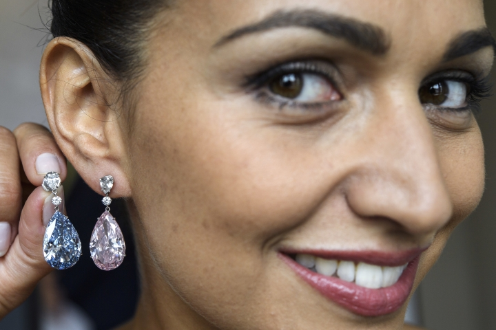 FILE - In this Thursday, May 11, 2017 file photo, a Sotheby's employee displays the Apollo blue diamond and the Artemis pink diamond earrings during a preview at the Sotheby's, in Geneva, Switzerland. Sotheby's sold a pair of pear-shaped diamond earrings at a hammer price of about $51 million Tuesday, May 16, 2017, though the 14.54-carat flawless Fancy Vivid Blue diamond that was the auction's highlight fell short of the expected range. (Martial Trezzini/Keystone via AP, File)