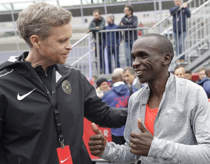 FILE - In this Saturday, May 6, 2017 file photo, Olympic marathon champion Eliud Kipchoge, right, talks with Nike CEO and President Mark Parker after crossing the finish line of a marathon at the Monza Formula One racetrack, Italy. Eliud Kipchoge was 26 seconds from making history on May 6. Nike and Adidas have announced separate plans to attack the 2-hour marathon, with both introducing shoe lines linked to the effort. Wireless tech giant Vodafone last month said it was backing a third bid, hoping data gleaned from the quest will translate into wearable technology. (AP Photo/Luca Bruno, File)