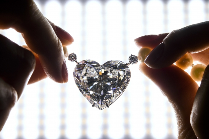 """FILE - In this Thursday, May 11, 2017 file photo, a Christie's employee displays The flawless heart-shaped Boehmer and Bassenge """"La legende"""" diamond during a preview at the Christie's, in Geneva, Switzerland. A heart-shaped diamond billed as the largest of its kind to go up for auction has sold for less than the pre-sale estimate, fetching a hammer price of 13 million Swiss francs (about $13.3 million.) The sale Wednesday, May 17, 2017 capped a two-day run of high-profile jewelry auctions in Geneva. (Martial Trezzini/Keystone via AP, File)"""