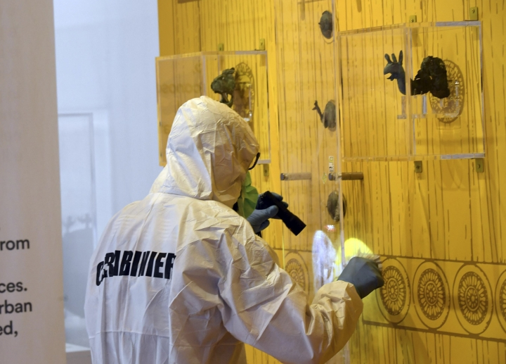 """A forensic officer inspects the point where an ancient ornamental bronze stud was stolen from the exhibit """"Pompeii and the Greeks"""" at the archaeological site of Pompeii, near Naples, southern Italy, Thursday, May 18, 2017. Officials said that the 6th Century stud, one of four that decorated a reproduction of an ancient door, was protected by a plexiglass panel. (Circo Fusco/ANSA via AP)"""