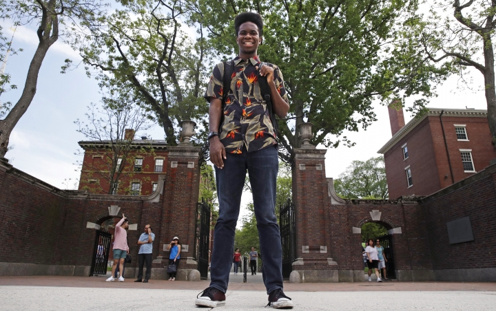 "Obasi Shaw poses outside the gates of Harvard Yard in Cambridge, Mass., Thursday, May 18, 2017. Shaw, an English major who graduates from Harvard next week, is the university's first student to submit his final thesis in the form of a rap album. The record, called ""Liminal Minds,"" has earned the equivalent of an A- grade, good enough to ensure that Shaw will graduate with honors at the university's commencement next week. (AP Photo/Charles Krupa)"