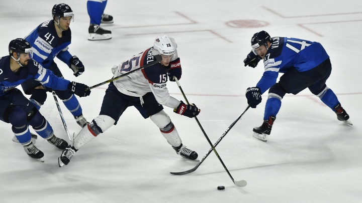 US forward Jack Eichel, center, Finland's defender Ville Lajunen, right, Finland's forward Juhamatti Aaltonen, left, and Finland's forward Antti Pihlstrom challenge for the puck at the Ice Hockey World Championships quarterfinal match between the United States and Finland in the LANXESS arena in Cologne, Germany, Thursday, May 18, 2017. (AP Photo/Martin Meissner)