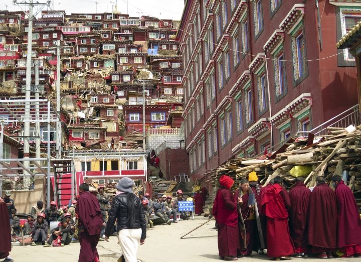 In this photo taken Monday, April 3, 2017, Tibetan Buddhist nuns and monks gather near demolition workers at the house and monastery complex built on the mountain also known as Sertar Buddhist Institution or Larung Gar in Sertar county, southwest China's Sichuan province. Chinese authorities in southwestern Sichuan province have evicted followers and razed scores of homes at one of the world's largest centers of Tibetan Buddhist learning in a months-long operation that has drawn protests from Tibetans in exile. (AP Photo/Charles Tay)