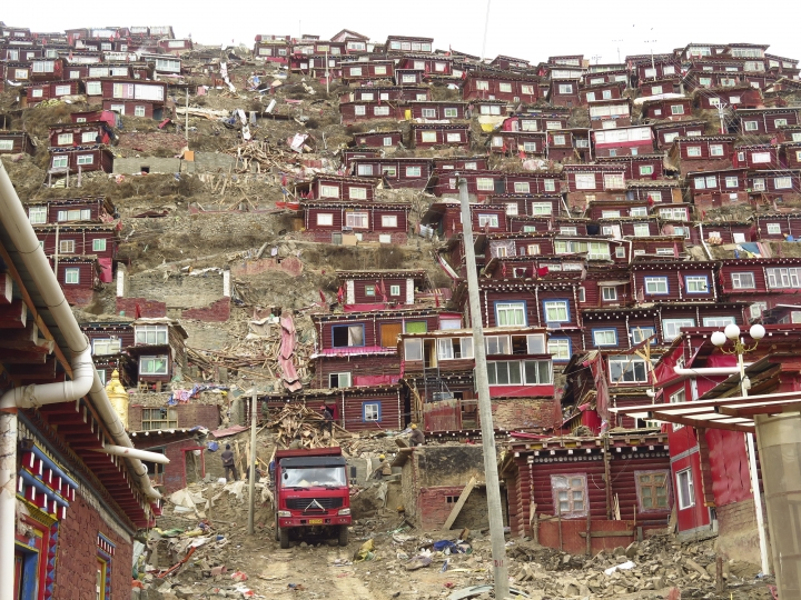 In this photo taken Monday, April 3, 2017, workers clear timber debris from a demolished part of the house and monastery complex built on the mountain also known as Sertar Buddhist Institution or Larung Gar in Sertar county, southwest China's Sichuan province. Chinese authorities in southwestern Sichuan province have evicted followers and razed scores of homes at one of the world's largest centers of Tibetan Buddhist learning in a months-long operation that has drawn protests from Tibetans in exile. (AP Photo/Charles Tay)