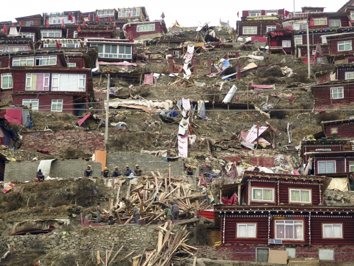 In this photo taken Monday, April 3, 2017, workers are seem near timber debris amongst a demolished part of the house and monastery complex built on the mountain also known as Sertar Buddhist Institution or Larung Gar in Sertar county, southwest China's Sichuan province. Chinese authorities in southwestern Sichuan province have evicted followers and razed scores of homes at one of the world's largest centers of Tibetan Buddhist learning in a months-long operation that has drawn protests from Tibetans in exile. (AP Photo/Charles Tay)
