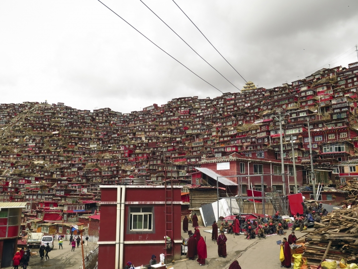 In this photo taken Monday, April 3, 2017, Tibetan Buddhist nuns and monks gather near demolition workers as Chinese tourists are seen at left at the house and monastery complex built on the mountain also known as Sertar Buddhist Institution or Larung Gar in Sertar county, southwest China's Sichuan province. Chinese authorities in southwestern Sichuan province have evicted followers and razed scores of homes at one of the world's largest centers of Tibetan Buddhist learning in a months-long operation that has drawn protests from Tibetans in exile. (AP Photo/Charles Tay)