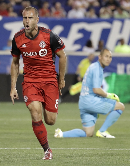 Toronto FC midfielder Benoit Cheyrou, left, runs while celebrating after scoring a goal on New York Red Bulls goalkeeper Luis Robles, right, during the second half of an MLS soccer match, Friday, May 19, 2017, in Harrison, N.J. (AP Photo/Julio Cortez)