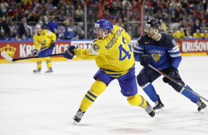 Sweden's Joakim Nordstrom, left, shoots to score his side's fourth goal, next to Finland's Oskar Osala at the Ice Hockey World Championships semifinal match between Sweden and Finland in the Lanxess arena in Cologne, Germany, Saturday, May 20, 2017. (AP Photo/Petr David Josek)