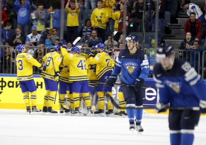 Swedish players celebrate at the end of the Ice Hockey World Championships semifinal match between Sweden and Finland in the Lanxess arena in Cologne, Germany, Saturday, May 20, 2017. (AP Photo/Petr David Josek)