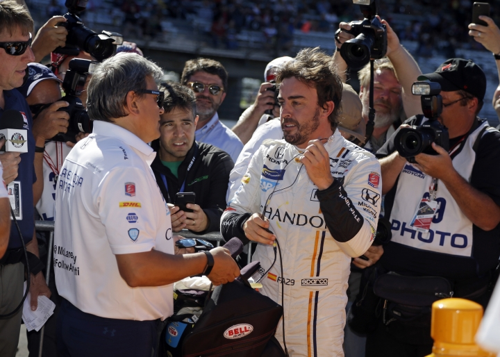 Fernando Alonso, center, of Spain, removes his gear after he qualified during qualifications for the Indianapolis 500 IndyCar auto race at Indianapolis Motor Speedway, Sunday, May 21, 2017, in Indianapolis. (AP Photo/Michael Conroy)
