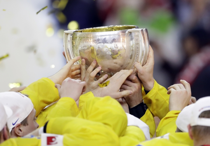 Sweden players celebrate with the trophy following the Ice Hockey World Championships final match between Canada and Sweden in the LANXESS arena in Cologne, Germany, Sunday, May 21, 2017. (AP Photo/Petr David Josek)