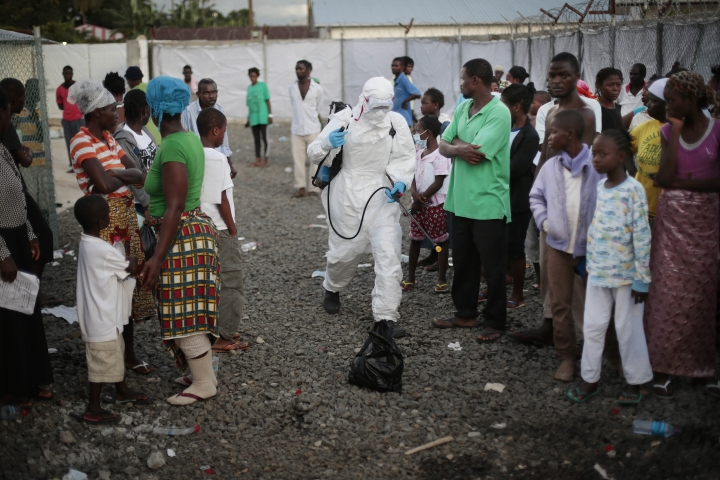 FILE - In this file photo dated Tuesday, Sept. 30, 2014, a medical worker sprays people being discharged from the Island Clinic Ebola treatment center in Monrovia, Liberia. The World Health Organization routinely spends about $200 million a year on travel, far more than what it doles out to fight some of the biggest problems in public health including AIDS, tuberculosis and malaria, according to internal documents obtained by The Associated Press, published Sunday, May 21, 2017. (AP Photo/Jerome Delay, File)