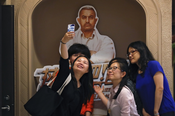 "In this Monday, May 22, 2017 photo, a group of Chinese women take a selfie with a poster of Indian Bollywood blockbuster film ""Dangal"" on display at a cinema in Beijing. The Aamir Khan film ""Dangal"" about an Indian man training his daughters to become wrestlers has become China's biggest grossing non-Hollywood foreign movie. The Indian film was released in China on May 5. By Tuesday, May 23, 2017, the Indian film had pulled in 806 million yuan ($117 million) in mainland China, according to data from EntGroup, a leading entertainment consultant. (AP Photo/Andy Wong)"