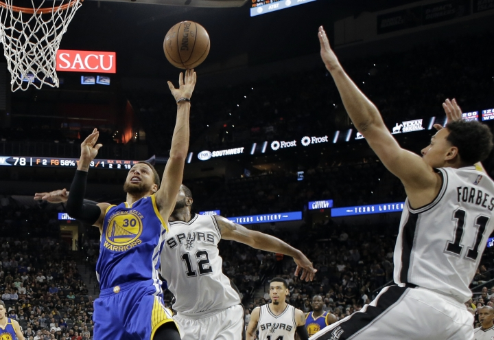 Golden State Warriors guard Stephen Curry (30) goes up for a shot as San Antonio Spurs' LaMarcus Aldridge (12) and Bryn Forbes (11) defend during the second half in Game 4 of the NBA basketball Western Conference finals, Monday, May 22, 2017, in San Antonio. (AP Photo/Eric Gay)