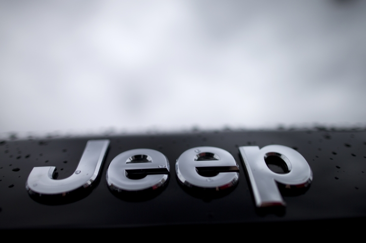 FILE - In this Dec. 2, 2014, file photo, raindrops dot the Jeep emblem on a Grand Cherokee SUV at a dealership lot, in San Diego. In a lawsuit filed Tuesday, May 23, 2017, the U.S. government is suing Fiat Chrysler, alleging that some diesel pickup trucks and Jeeps cheat on emissions tests. The Justice Department lawsuit alleges that nearly 104,000 Ram pickups and Jeep Grand Cherokees from the 2014 to 2016 model years have software that allows them to emit lower amounts of pollutants during lab tests by the Environmental Protection Agency than during normal driving conditions. (AP Photo/Gregory Bull, File)