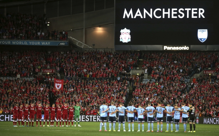 Liverpool FC, left, and Sydney FC pause for a minute's silence before their friendly soccer match as a tribute to the victims of a bombing at Manchester, in Sydney, Wednesday, May 24, 2017. (AP Photo/Rick Rycroft)
