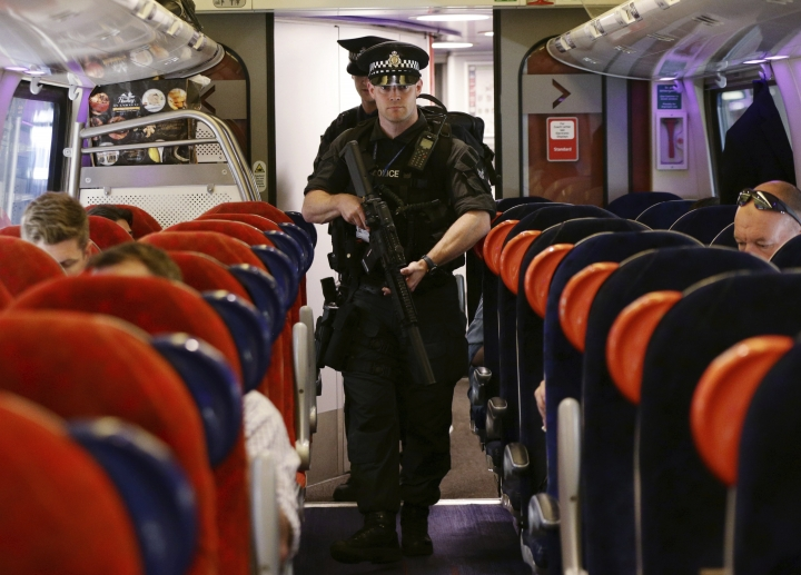 """Armed British Transport Police Specialist Operations officers on board a train to Birmingham New Street at Euston station in London as armed police officers are patrolling on board trains nationwide for the first time Thursday May 25, 2017. British Transport Police announced the measure in a bid to """"disrupt and deter criminal activity"""" on the rail network after the UK terror threat level rose to critical in the wake of the Manchester attack. (Yui Mok/PA via AP)"""